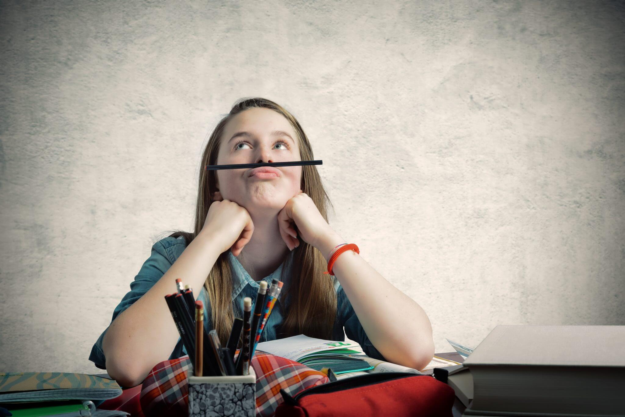 Student thinking while balancing a pencil on the top of her lip